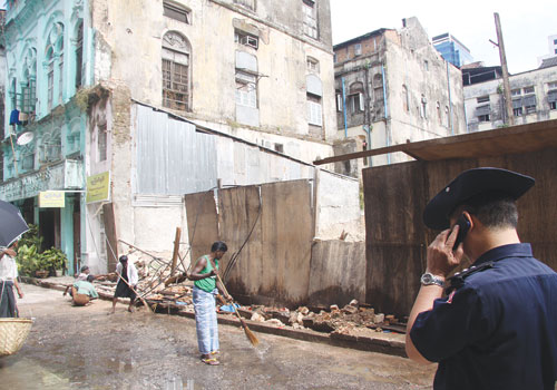 Men tidy the street beside a redevelopment of a 'dangerous' building site in Pabedan township last week.