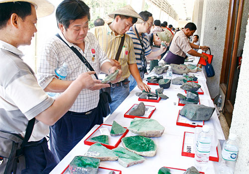 Traders inspect jade at a gem emporium in Yangon in 2004.  Hein Latt Aung / The Myanmar Times