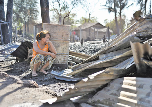 A woman looks at the remains of her home in Hlaing Tharyar township last week. Kaung Htet / The Myanmar Times