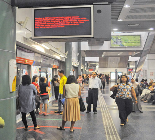 Commuters wait for a train at Sengkang station on Singapore's northeast line on March 15 as a screen shows the train service between Harbourfront and Outram Park not functioning due to a power outage.AFP/ The Myanmar Times