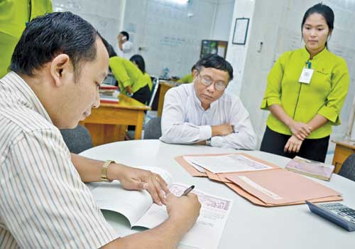 A client signs an agreement at Sai Khung Noung real estate agency in Tarmwe township last week. Boothee / The Myanmar Times
