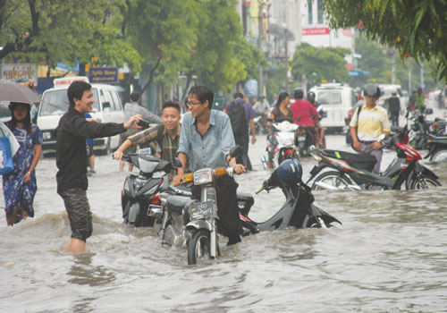 Motorcyclists negotiate a flooded 30th Street in downtown Mandalay, near the University of Medicine, following heavy rain on the evening of September 4, the first significant rainfall in Mandalay during the monsoon season. A government weather station in the city recorded 3.70 inches of rain for the day. Phyo Wai Kyaw/ The Myanmar Times