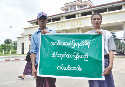 Protesters hold signs in front of FMI City in Hlaing Tharyar township. Kaung Htet Linn / The Myanmar Times
