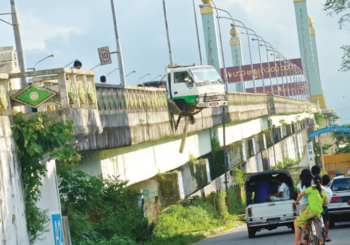 The Canter light truck hangs off the edge of Mahabandoola Bridge in Dawbon township on September 15. Boothee / The Myanmar Times