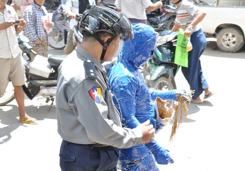 A police officer stops Suu Myint Thein in Mandalay on September 20. Photo: Supplied