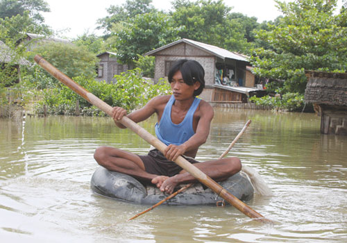 A resident paddles on a tyre tube in Padanmyar village. Phyo Wai Kyaw / The Myanmar Times