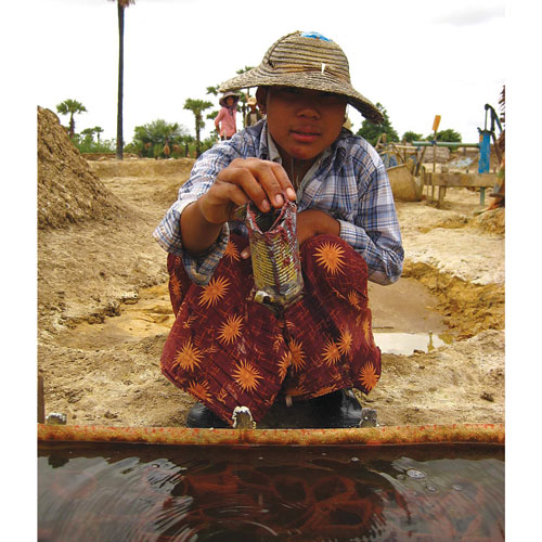 Ma Aye Aye demonstrates the process of extracting copper from ponds at a mine site near Monywa in 2008. Minh Zaw / The Myanmar Times