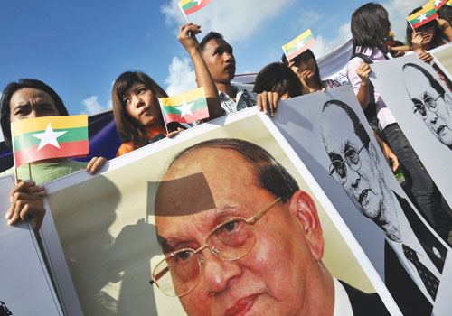 Supporters hold pictures of President U Thein Sein awaiting his arrival at Yangon International Airport last week.  Photo: AFP