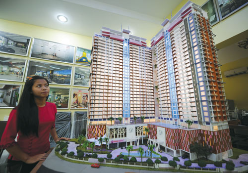A Mandalay Golden Wings Construction employee stands next to a model of the company's Diamond Inya Palace development last week, October 2012.  (Ko Taik / The Myanmar Times)