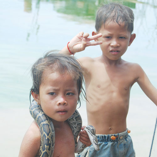 Kids carry a python at Tonle Sap lake in Cambodia. Douglas Long/ The Myanmar Times