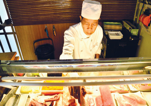 A chef slices up raw fish at Hello Maki and Sushi at one of their two branches on Inya Road. (Nyein Maung / The Myanmar Times / Monday, November 12, 2012)