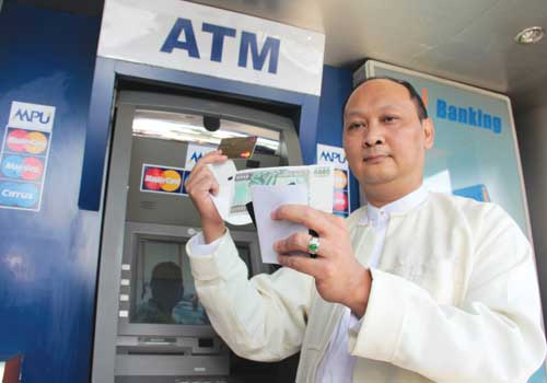 Co-operative Bank executive chairman and chief executive officer U Kyaw Lynn displays cash withdrawn from an ATM at the bank's headquarters in Yangon Thursday, November 15, 2012. (Thiri Lu / The Myanmar Times)