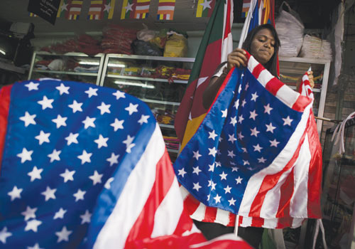 A woman folds US national flags at a shop in Yangon Friday, November 16, 2012. (AFP)