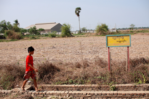 A child walks past land sold to Wah Wah Win for the construction of Anawrahta Industrial Zone Monday, April 28, 2012 (Boothee / The Myanmar Times)