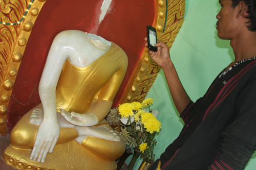 A villager snaps a shot of one of three beheaded Buddha statues in Inwa Wednesday, December 12, 2012. (Phyo Wai Kyaw/The Myanmar Times)