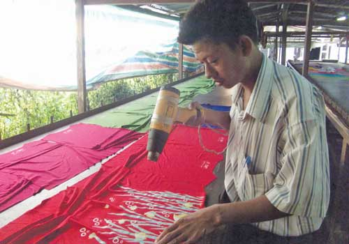 An A Plus Three employee dries a t-shirt at the company's factory in Hlaing township in December 2012. (Soe Sandar Oo/The Myanmar Times)