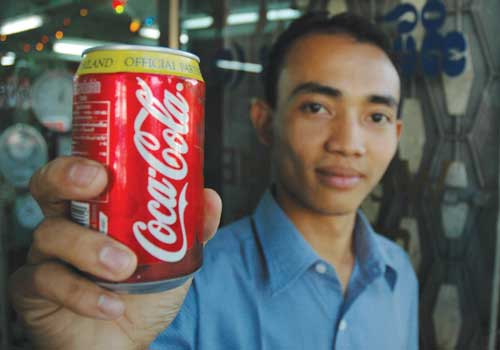 A man holds a can of Coca-Cola in downtown Yangon earlier this year. American giants Coca-Cola, Pepsi and General Electric have all responded to the easing of sanctions by entering Myanmar. (Stuart Deed/The Myanmar Times)