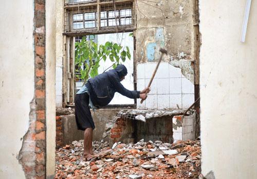 A worker deconstructs the building at 233-235 Pansodan Street in October 2012, before demolition was halted following a media campaign by heritage activists. (Boothee/The Myanmar Times)