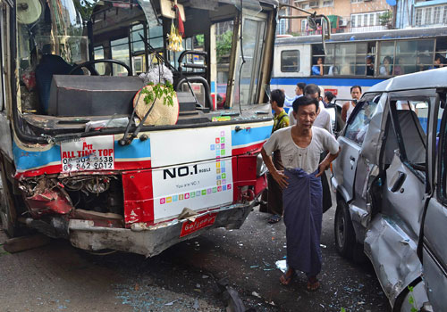A man stands between a bus and a van involved in a nine-vehicle crash in Yangon on December 31, 2012 that left five people injured. (Ye Naung/The Myanmar Times)
