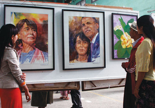 Patrons examine pictures at the 'Mandalay Yenantthit 2' exhibition December 25, 2012. (Si Thu Lwin/The Myanmar Times)