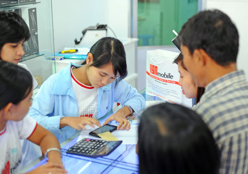 A clerk at YGN Mobile prepares a mobile handset for clients. (Ko Taik/The Myanmar Times)