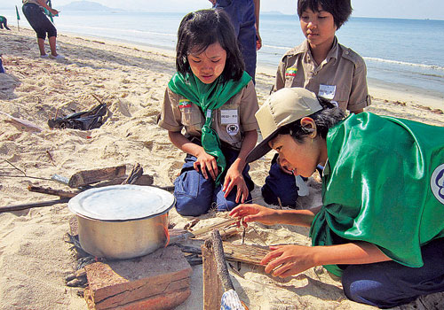 Students from Basic Education High School 3 Dawei cook rice at Maungmakan Beach in December 2012 under a scouting program being trialled by the Ministry of Education. (Cherry Thein/The Myanmar Times)
