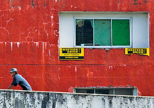A worker walks by Western Union signs in downtown Yangon. (Bloomberg)