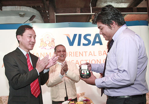 Somboon Krobteeranon (left), visa country manager for Myanmar and Thailand, uses his Visa card to purchase a souvenir from Ko Thet Lynn Aung of Green Elephant Restaurant and Showroom in Yangon's Kamaryut township on January 31. Photo: Supplied