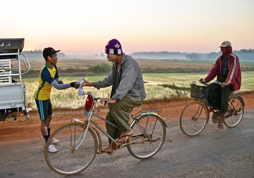 Members of Green Bike hand out leaflets to villagers during their ride from Yangon to Dawei. Photo: Marcus Rhinelander