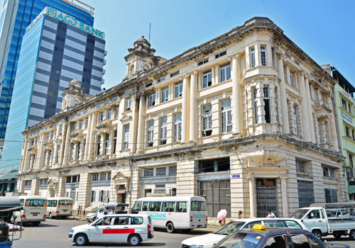 A colonial era building alongside Asia Green Development Bank's head office on Sule Pagoda Road. (Aung Htay Hlaing/The Myanmar Times)