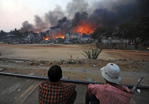 Residents sit on a railway track watching buildings burn around a mosque in riot-hit Meiktila on March 21. Photo: AFP
