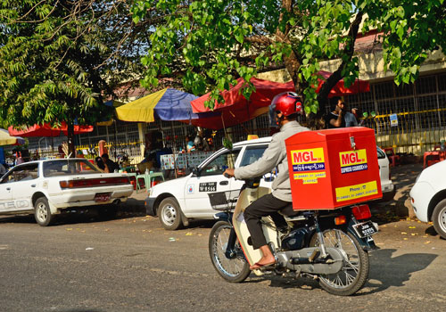 Would you like a fine with that? A courier takes a chance in Yangon. (Boothee/The Myanmar Times)