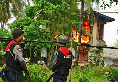 Police watch as a house burns down during communal conflict in Sittwe, Rakhine State, in June last year. (Boothee/The Myanmar Times)