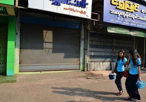 Two women walk past shuttered ground floor shops at Yuzana Plaza on March 25. (Aung Htay Hlaing/The Myanmar Times)