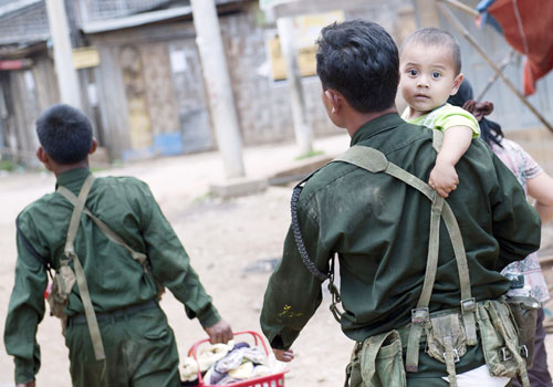 A soldier carries a child to a monastery in Lashio on May 30, following a fresh outbreak in violence that left one dead and at least four injured. Photo: AFP