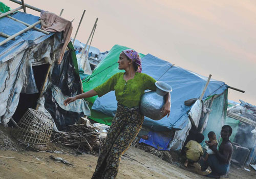 A Muslim woman walks past shelters in an IDP camp in Sittwe last month. (Aung Htay Hlaing/The Myanmar Times)