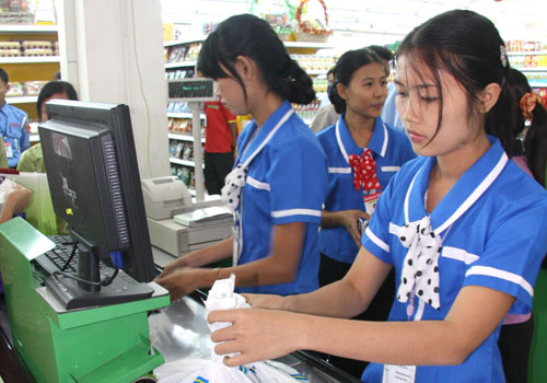 Cashiers at work at grocery store in Yangon. Photo: Staff