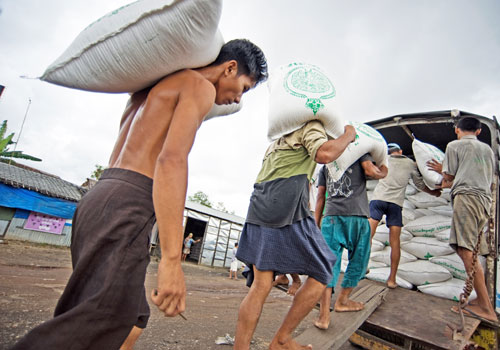 Workers in Ayeyarwady Region load sacks of rice on a truck bound for Yangon. Poor transport is hindering the growth of the agricultural sector. Photo: Kaung Htet