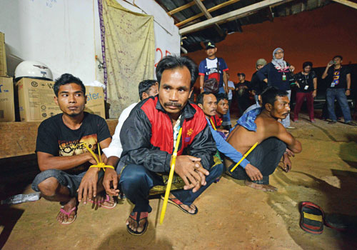 Suspected illegal foreign workers sit on the ground during an immigration raid operation shortly after midnight on September 1 outside Kuala Lumpur. Photo: AFP