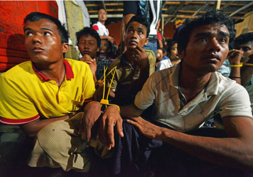 Detained migrants, their hands bound, sit on the ground following a raid by immigration officials near Kuala Lumpur shortly after midnight on September 1. Photo: AFP