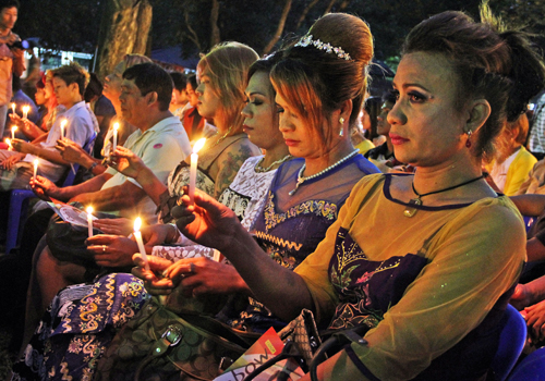 Several women hold candles while observing a moment of silence in People's Park in Yangon. Photo: Zarni Phyo