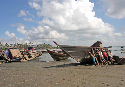 Fishermen try to push a boat into the sea after repairing it in Ngapudaw township, Ayeyarwady Region. Photo: AFP