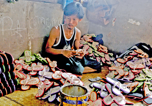 A sandal maker, who started his family's business using a microfinance loan, sits at his makeshift workplace at his home in Yangon. Photo: Philip Heijmans