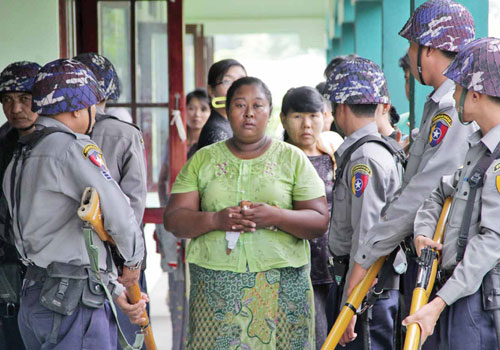 The mother of Ko Kyaw Zin Htet, one of four men sentenced to 10 years' imprisonment for murdering U Soe Min Htwe in July, stands beside police outside court on October 14. (Si Thu Lwin/The Myanmar Times)