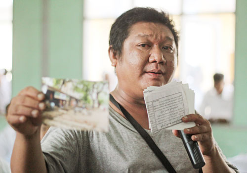 A resident shows documents and photographs indicating that he paid for an application for ownership of his house in 1992. (Sithu Lwin/The Myanmar Times)