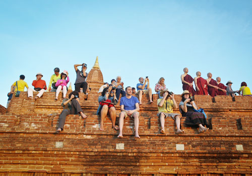 Tourists and Myanmar visitors watch the sun set from the top of a temple at Bagan. (Yu Yu/The Myanmar Times)