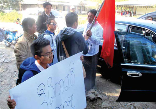 U Tin Lin Maung grabs a flag during a student protest on January 13. (Mg Zaw/The Myanmar Times)