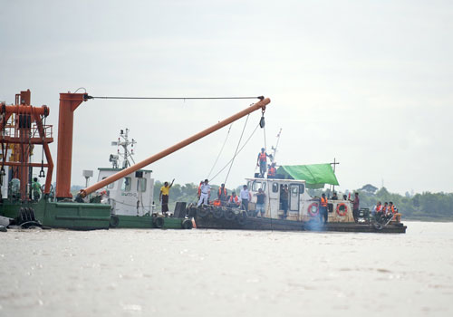 Members of a team searching for the Dhammazedi Bell stand on a dredger in the Yangon River on August 27, 2014. Photo: AFP