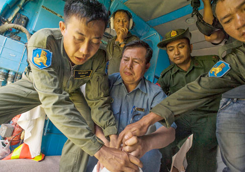 U San Shwe Aung (centre, in blue), permanent secretary of the Ministry for Border Affairs, drops supplies from an air force helicopter to flooded villages in Rakhine State yesterday. (Kaung Htet/The Myanmar Times)