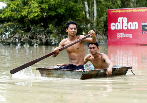 Residents paddle through floodwaters in Kalay, Sagaing Region, yesterday. Photo: AFP